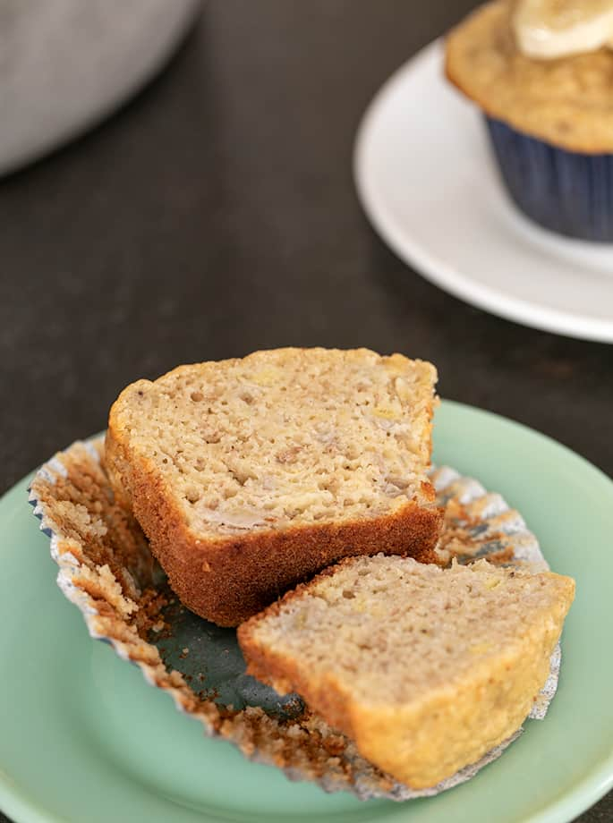 Banana muffin sliced in half on small green plate with muffin on small white plate in background