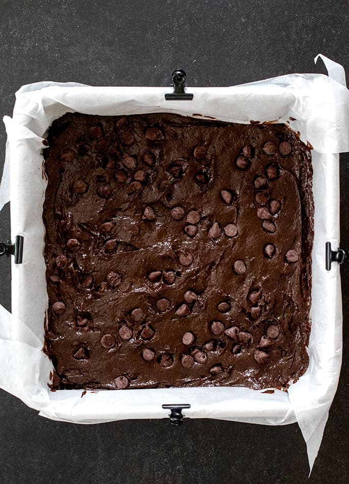 Chocolate cake batter in square cake pan lined with white paper