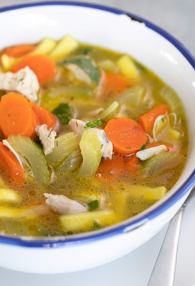Closeup image of chicken noodle soup in white bowl with blue rim