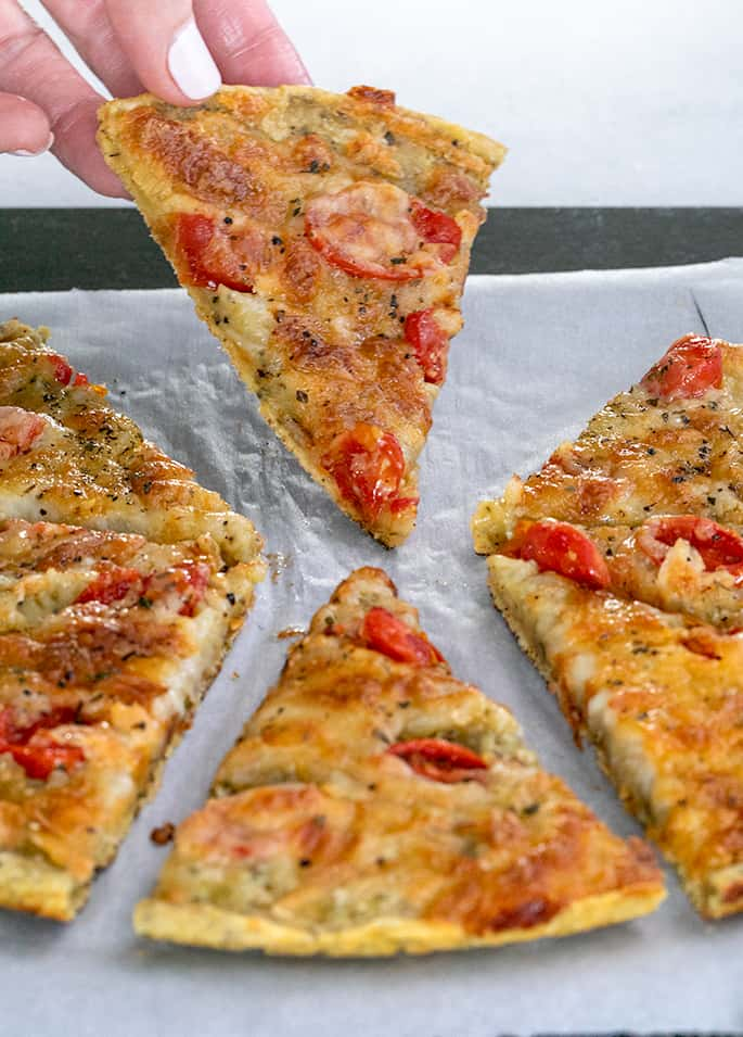 Fingers holding up a slice of chickpea pizza with other slices on white paper