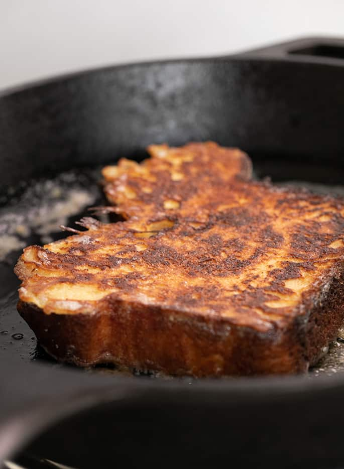 French toast slice frying in butter in black cast iron pan