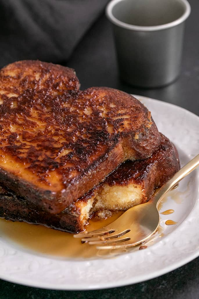 French toast with syrup on plate with one bite taken and fork on side