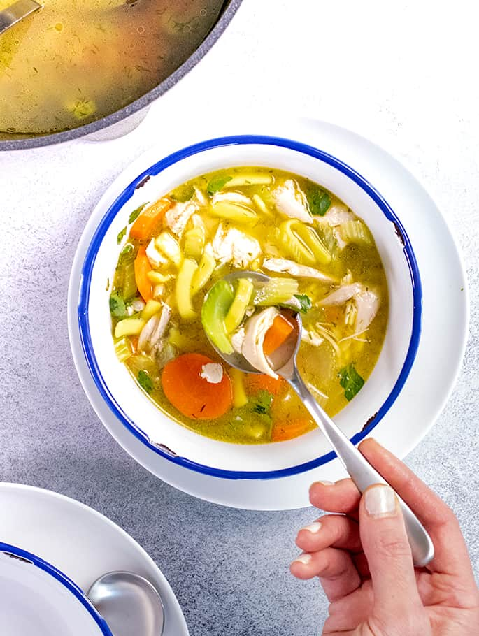 Hand holding spoon with spoonful of chicken noodle soup in white bowl with blue rim
