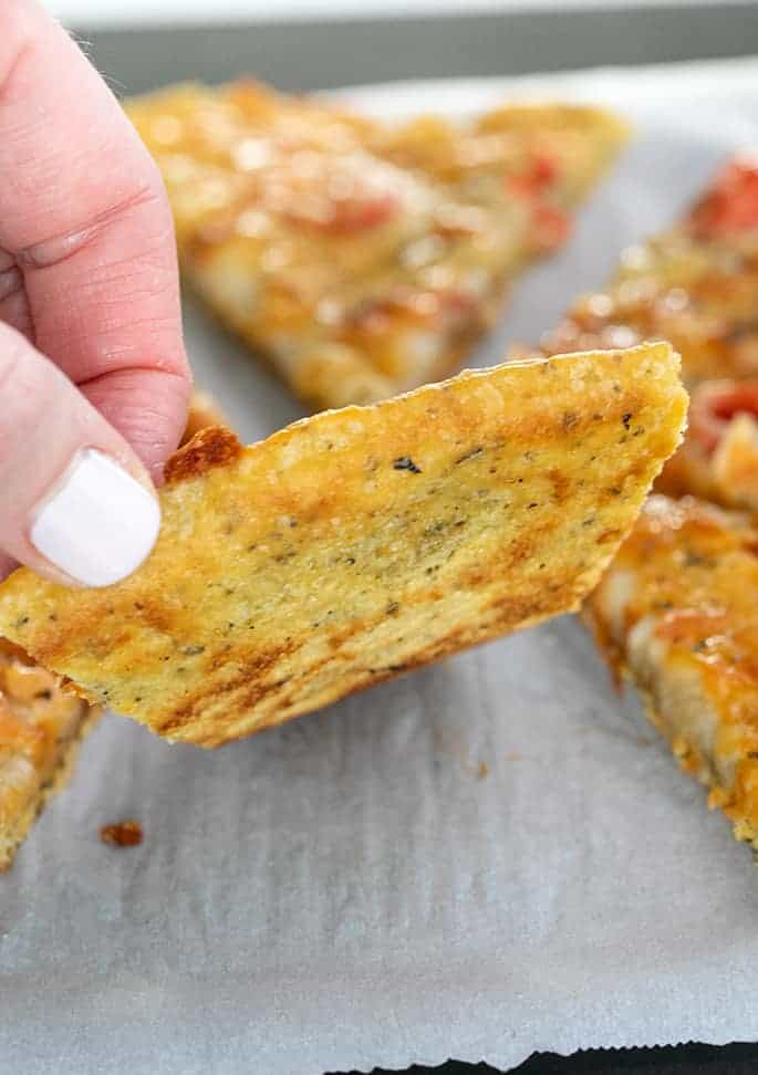 Hand picking up slice of chickpea pizza to show underside of slice on white paper