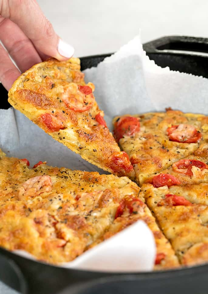 Hand picking up slice of chickpean pizza from cast iron skillet lined with paper