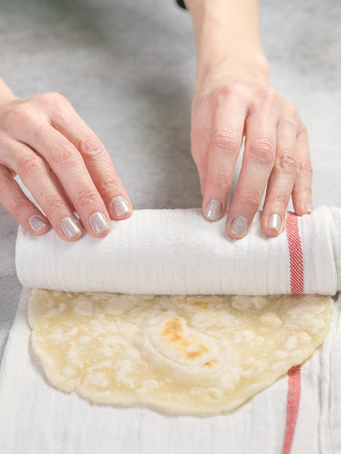 Hands rolling flatbread in a white towel with a red stripe