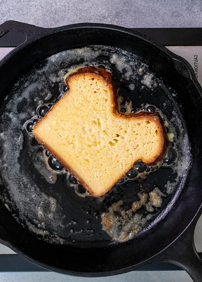 Overhead image of one slice of bread frying in a cast iron skillet with butter