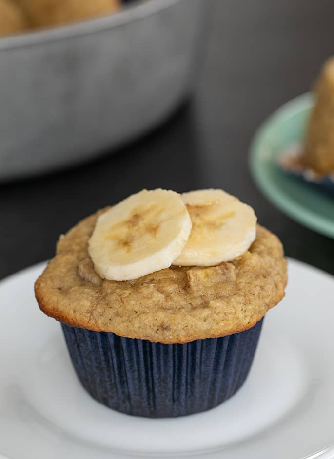 Whole almond flour muffin on small white plate with two banana slices on top