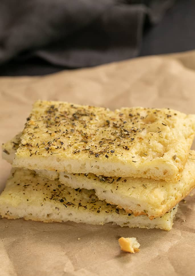 side image of 3 pieces of herb focaccia on brown paper with a large crumb