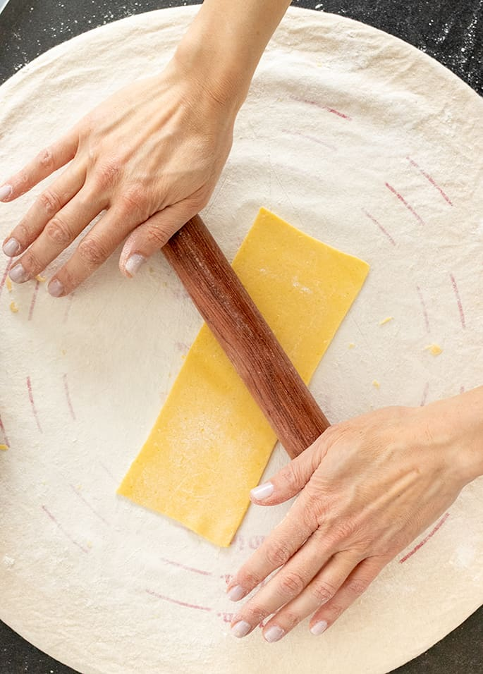 Hands on a small brown rolling pin rolling a piece of pasta dough on a round cloth
