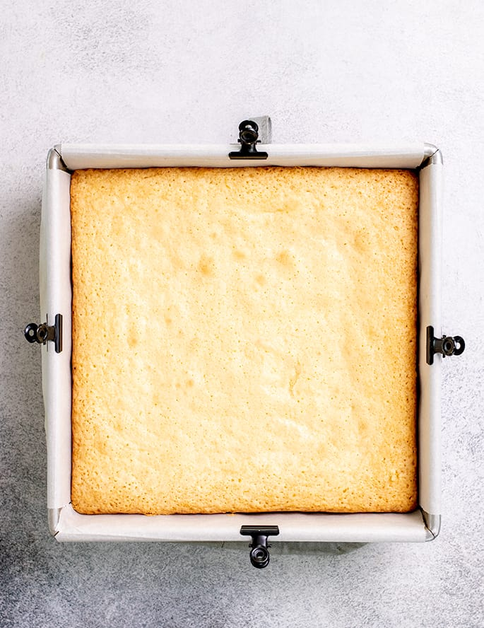 Baked lemon brownies in square pan with white paper lining