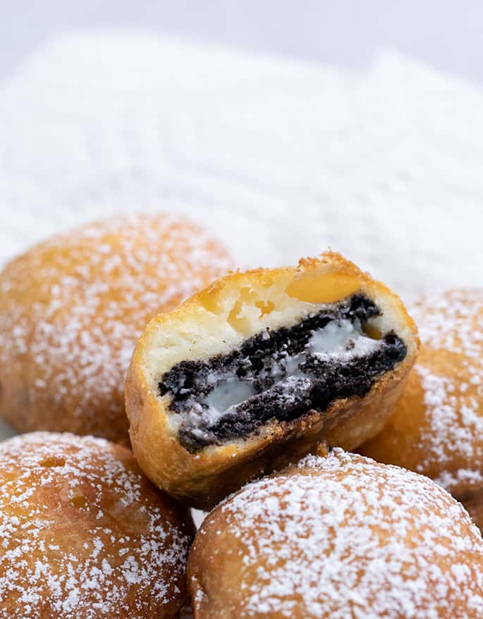 Fried Oreo cut in half with melting inside on top of whole fried Oreos