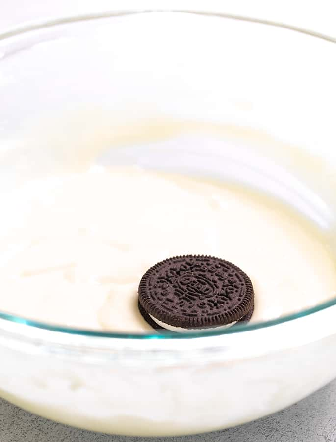 Glass bowl of pancake batter with one Oreo on top