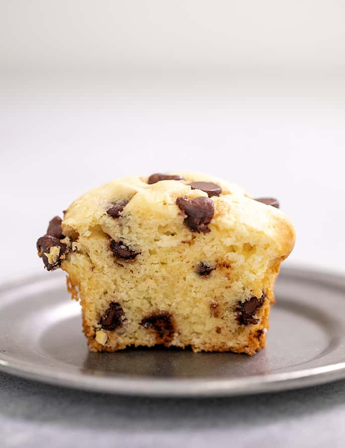 Half of a chocolate chip muffin on a small pewter plate
