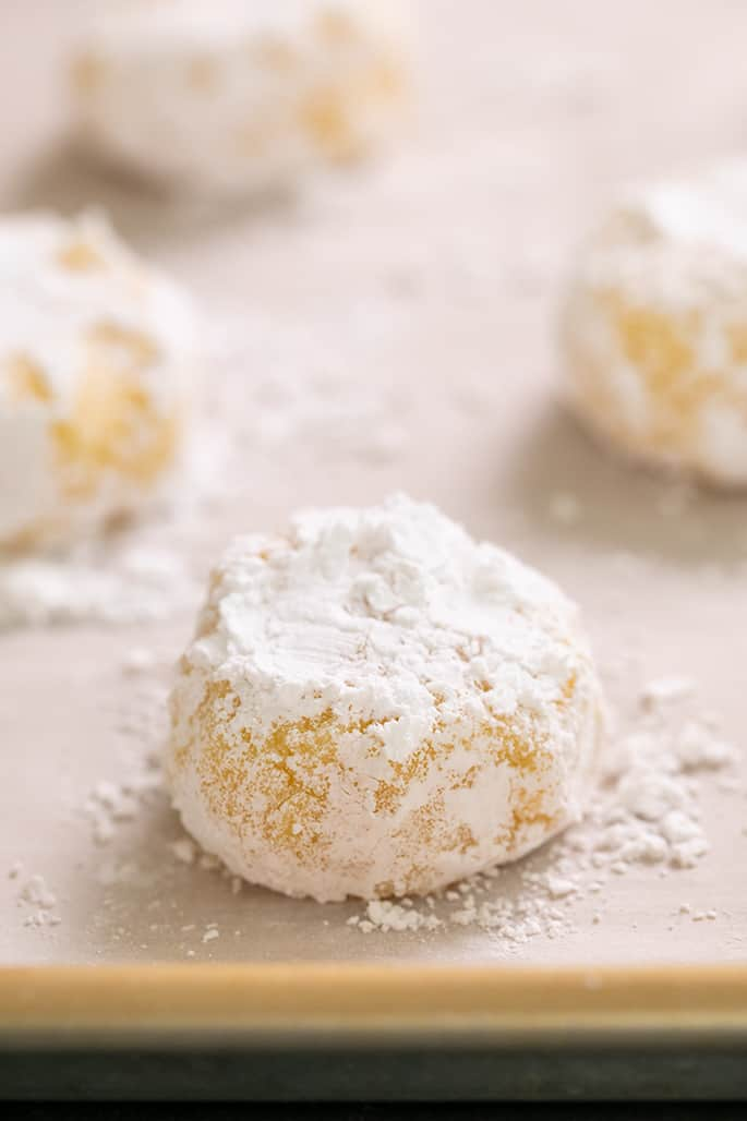 Raw mounds of lemon crinkle cookie dough with confectioners' sugar on white paper on tray
