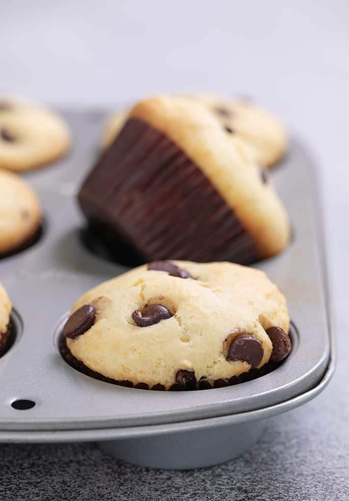 Six chocolate chip muffins in a muffin tin with one on its side