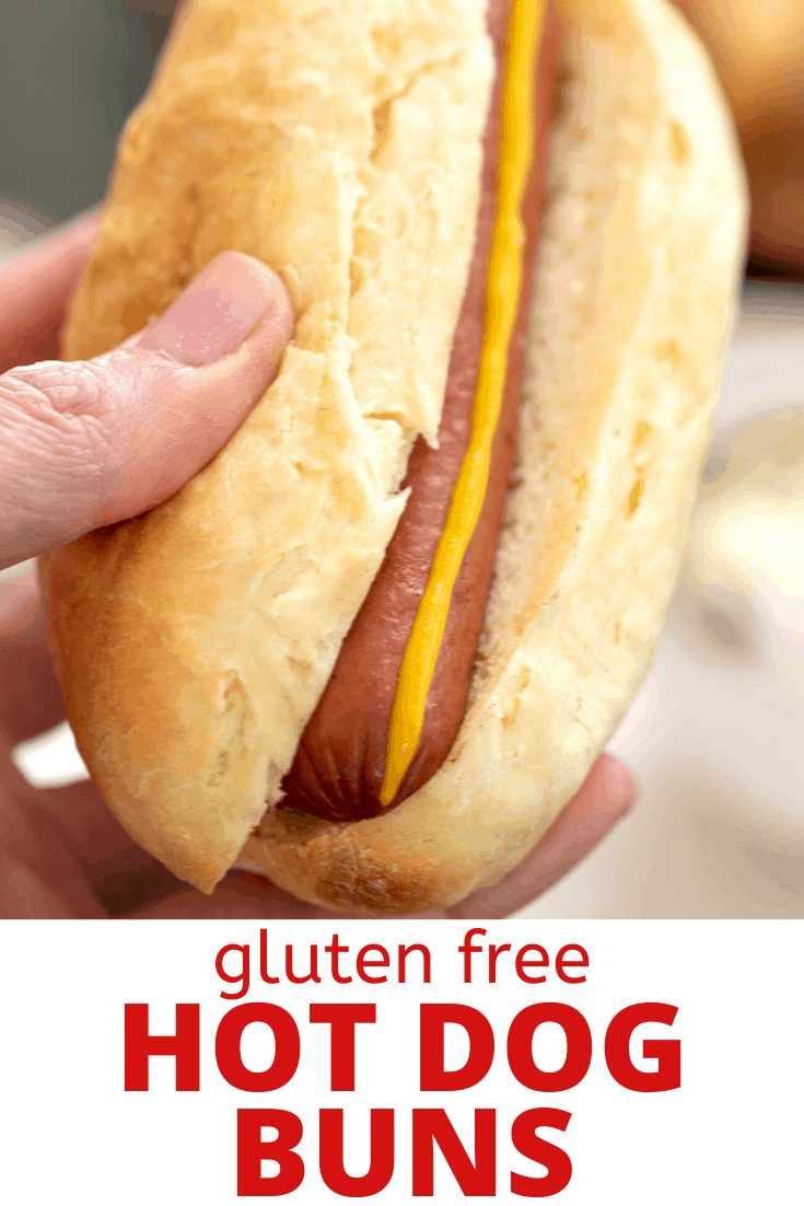 Words gluten free hot dog buns and image of hand holding hot dog with mustard stripe in bun