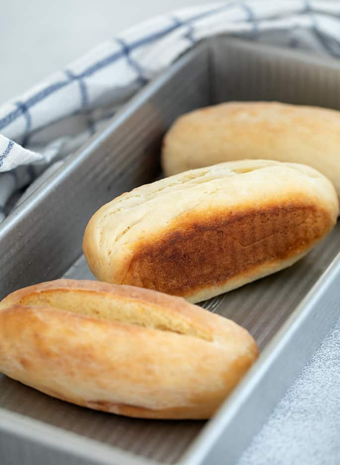 hot dog buns in rectangular metal pan with blue and white checked tea towel