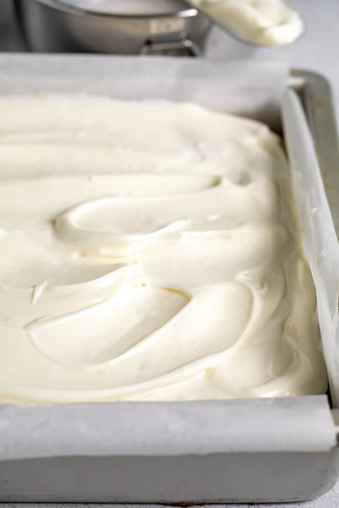 Closeup image of white frosted cake in square metal dish with more frosting in background