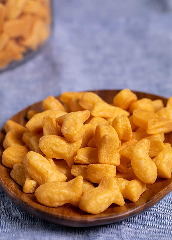 Goldfish shaped crackers in a pile on a small brown acacia plate on blue cloth