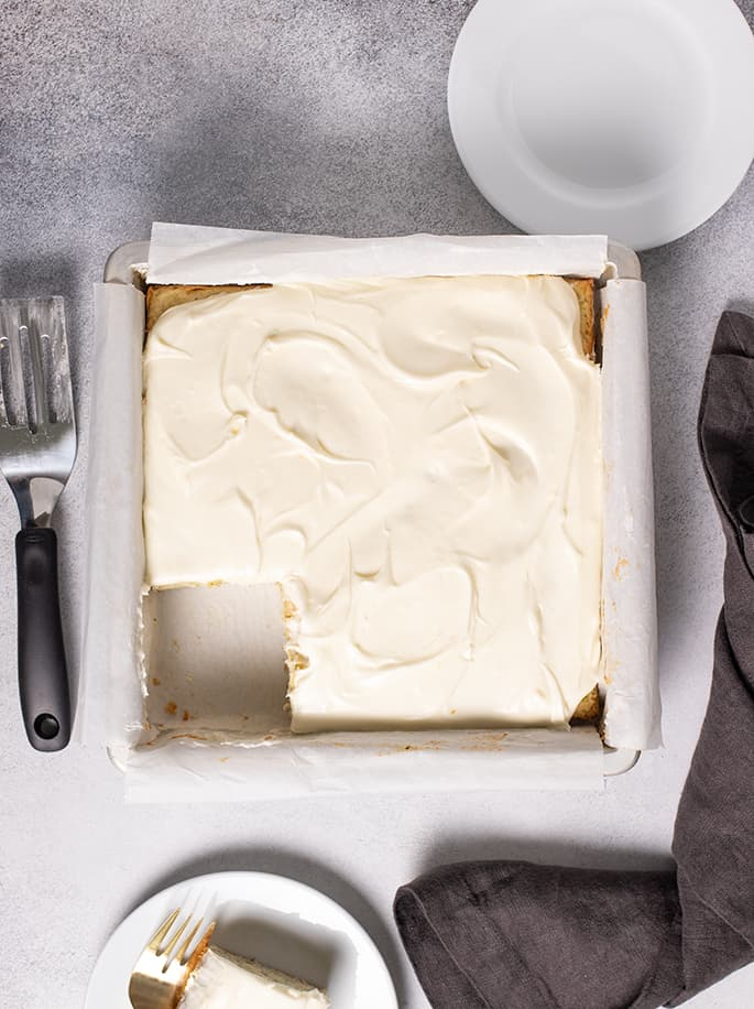 Overhead image of frosted zucchini cake in square pan with two small white plates and dark gray cloth