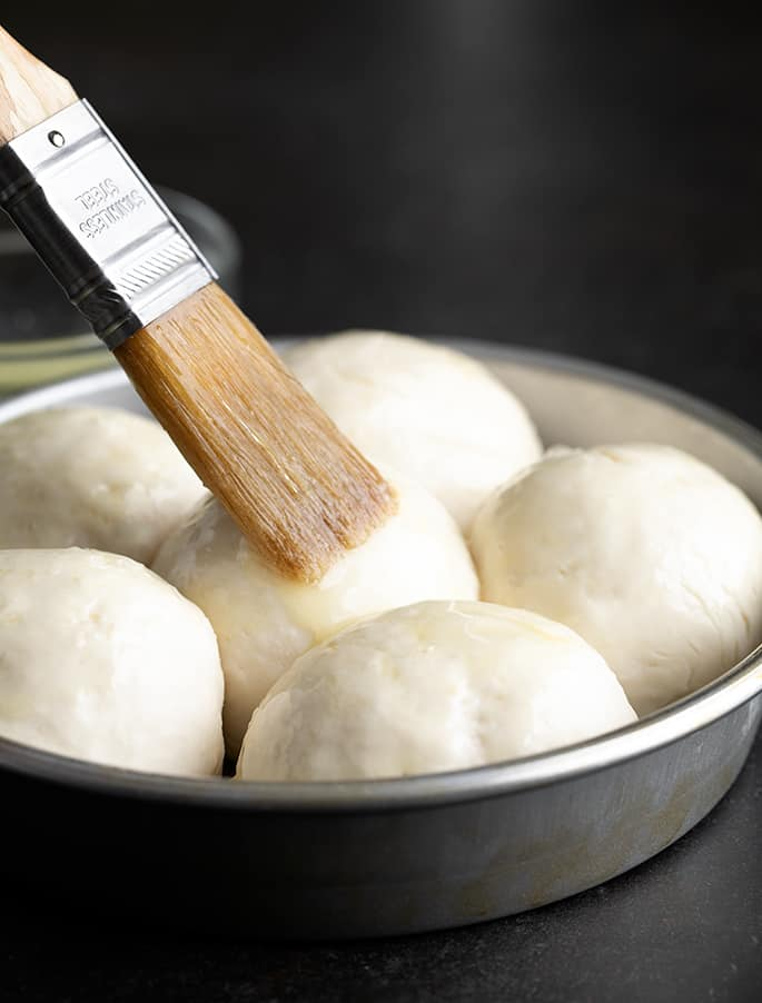 Pastry brush placing melted butter on center roll in round metal baking dish with 6 raw rolls