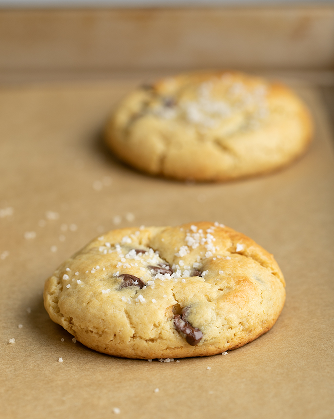 Two baked chocolate chip cookies with salt on brown paper on tray