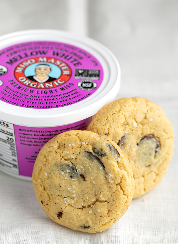 Two chocolate chip cookies leaning against a round container of mellow white miso paste on a white cloth