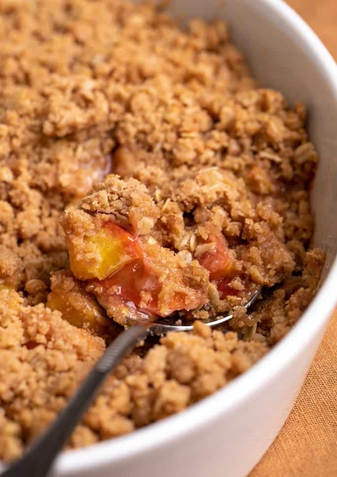 Closeup image of serving spoon in white serving dish of peach crisp
