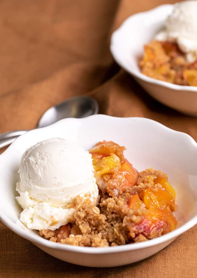 Crispy crumble topping and cooked peach filling with scoop of vanilla ice cream in white bowl on brown cloth