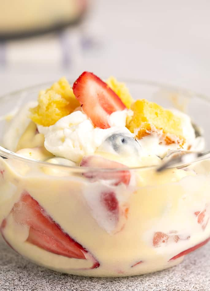 Custard, pound cake, strawberries, and whipped cream in small glass bowl with spoon