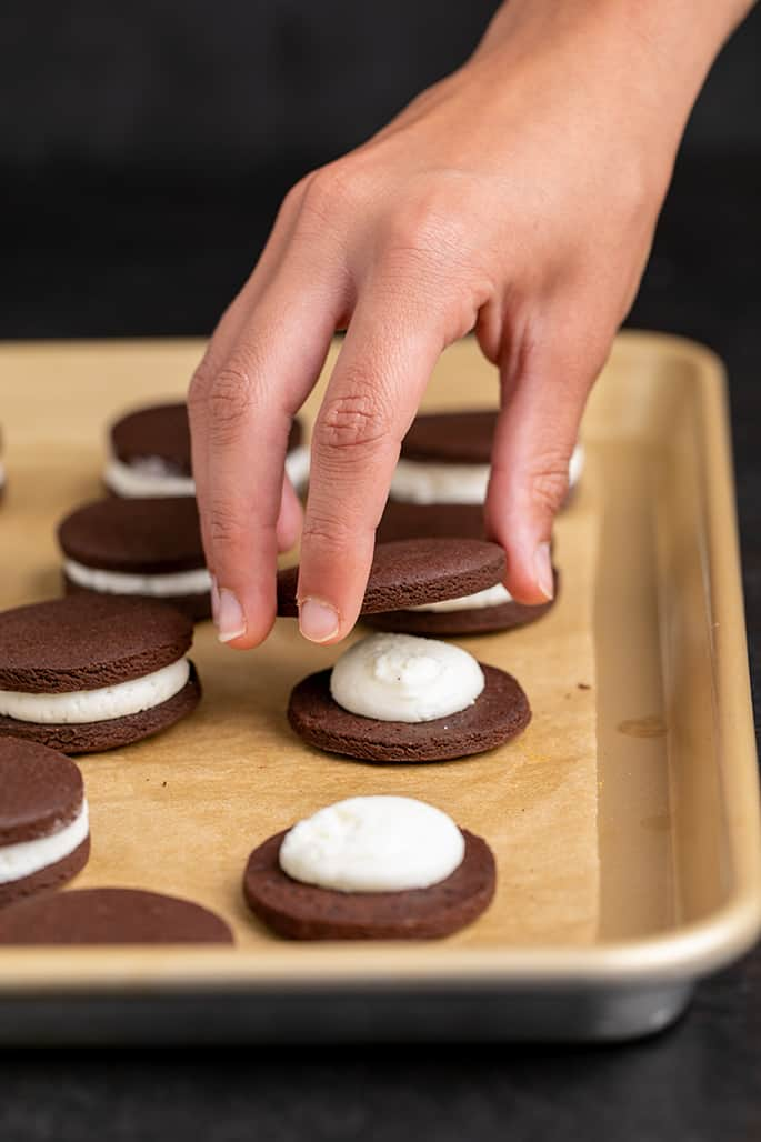 Hand holding a baked round chocolate cookie and placing it on top of filling that's on another cookie