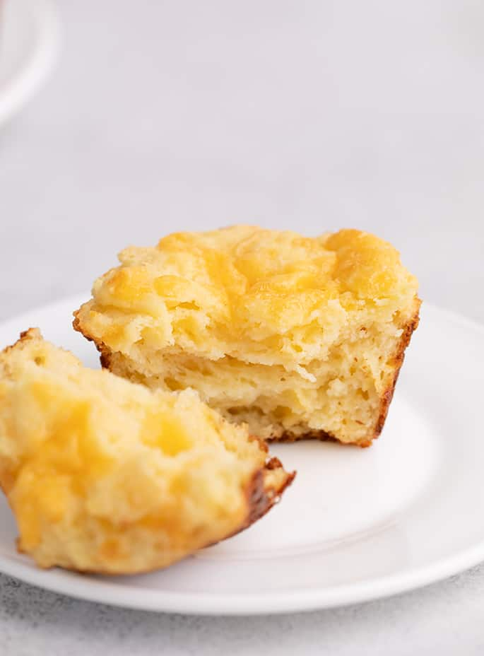 Muffin torn in half on small white plate on white table