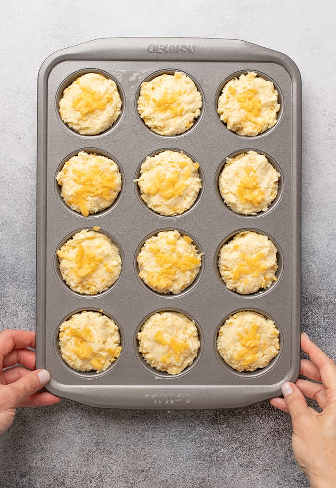 Overhead image of hands in corners of muffin tin with raw yellow batter in wells