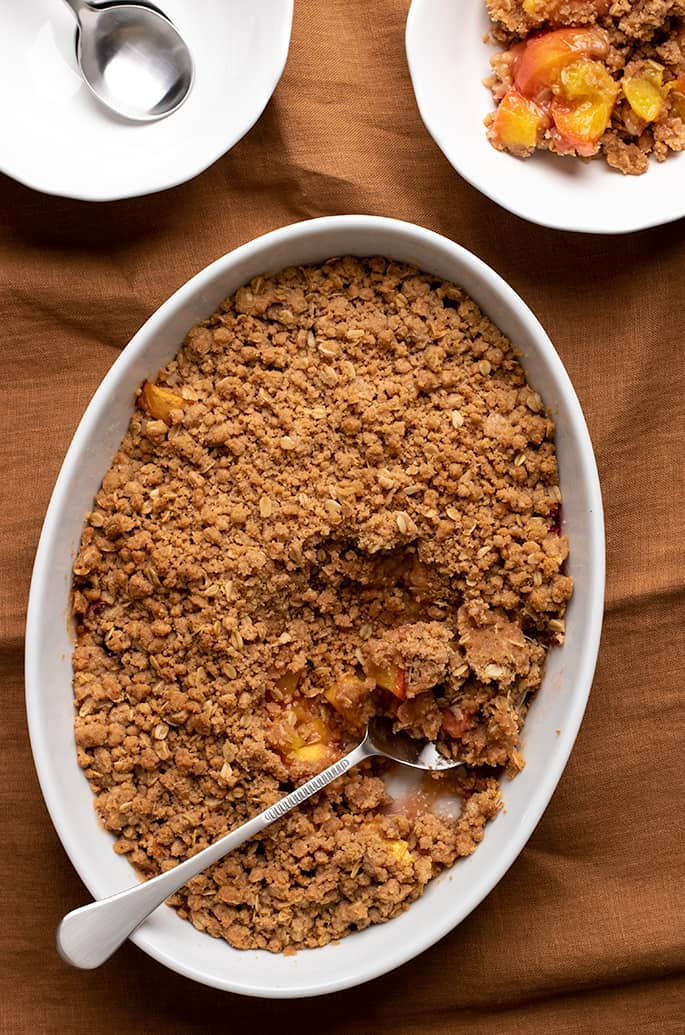 Overhead image of peach crisp in white oval serving dish with serving spoon and two small white bowls one with a serving