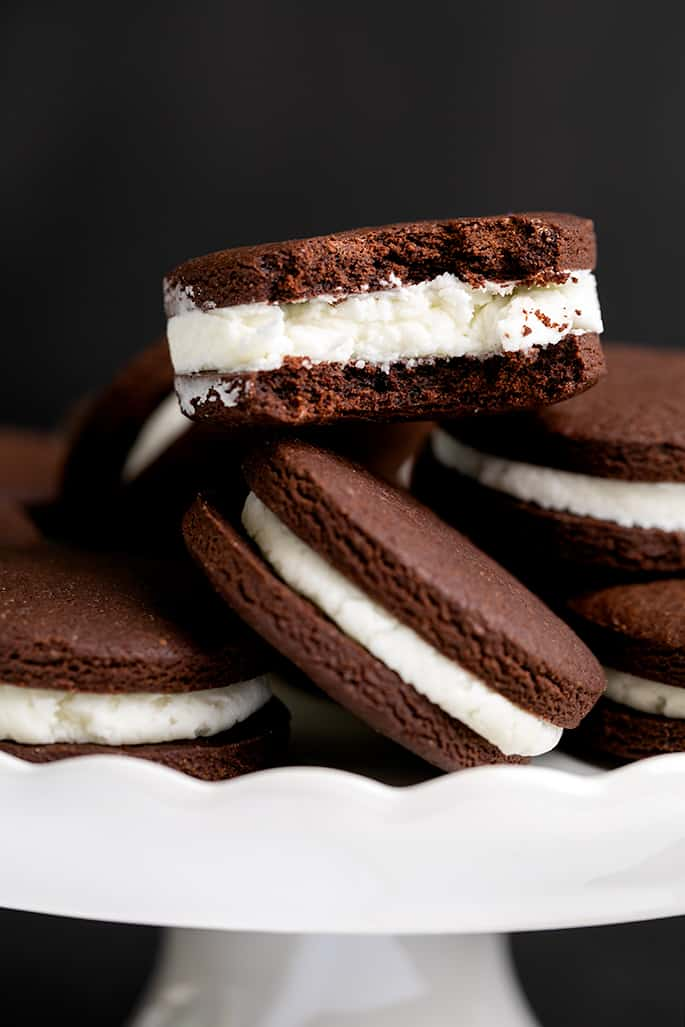 Pile of chocolate sandwich cookies with white filling on a white scalloped cake plate with one cookie on top with a bite taken