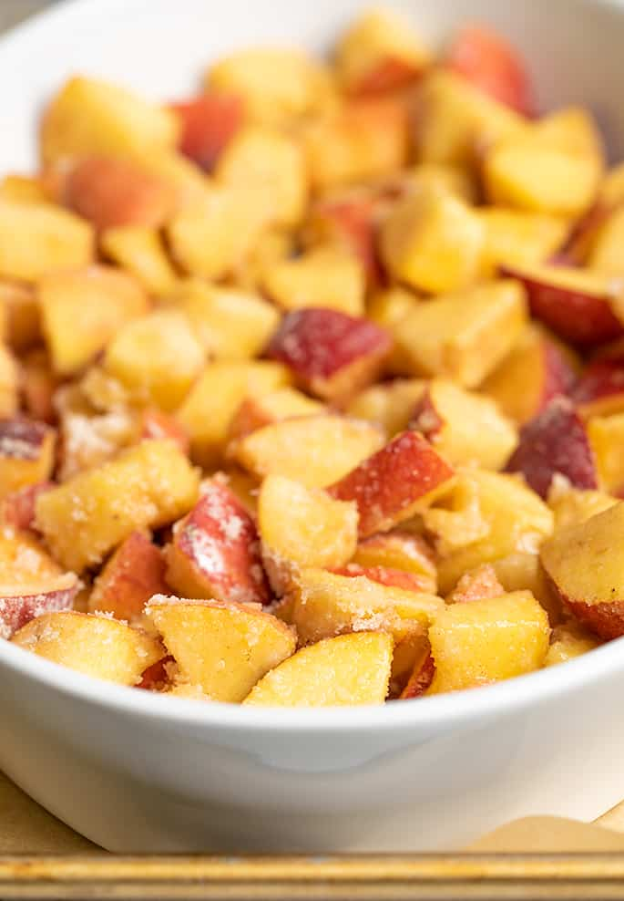 Raw chunks of peaches in oval white baking dish on metal tray