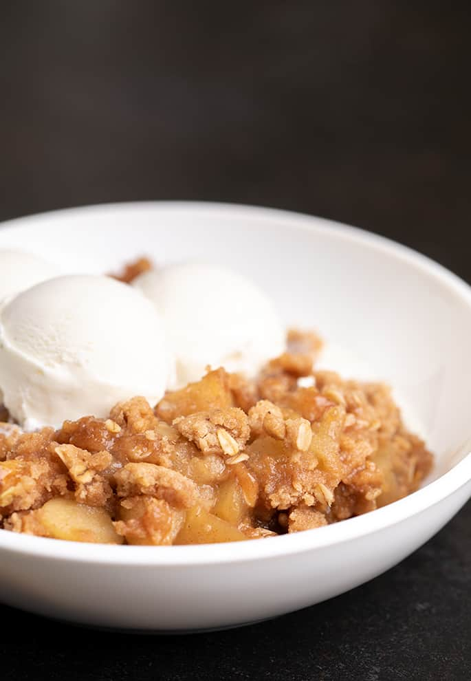 Baked apples and crisp topping with two scoops of vanilla ice cream in a round white bowl on a black background