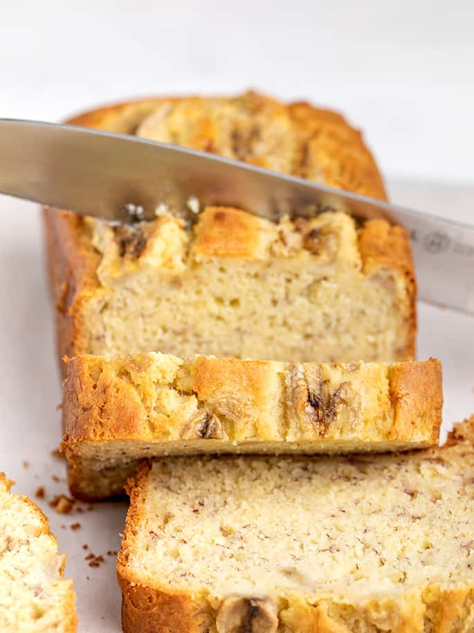 Banana bread with bananas on top being sliced with large knife