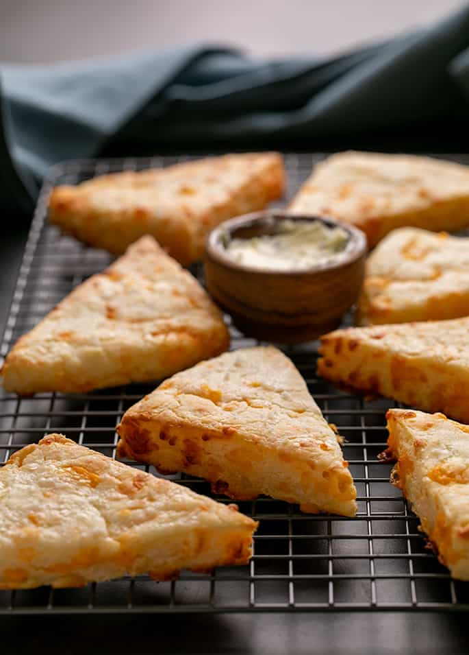 Cheese scones on wire rack on black surface with blue cloth in background
