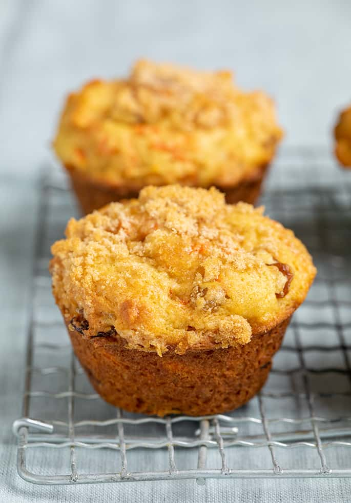 Closeup image of carrot muffin on wire rack on light blue cloth