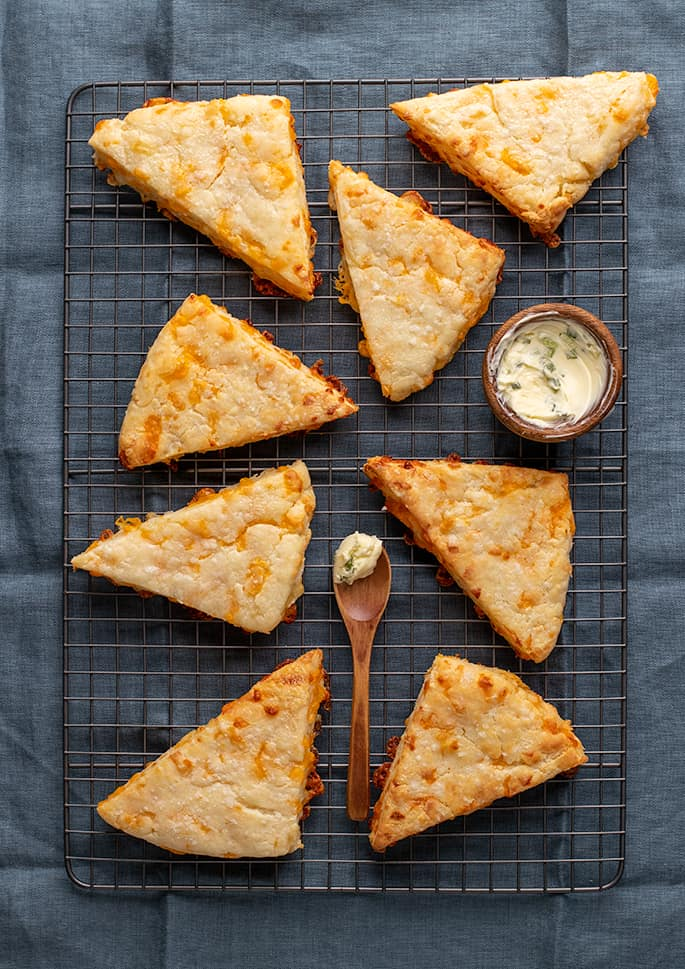 Overhead image of 8 cheese scones with butter on wire rack on blue cloth