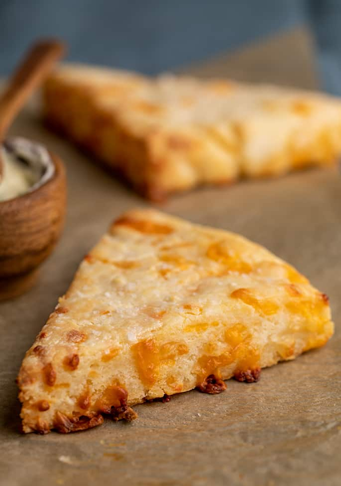 Two cheese scones on brown parchment paper with a wooden bowl and spoon