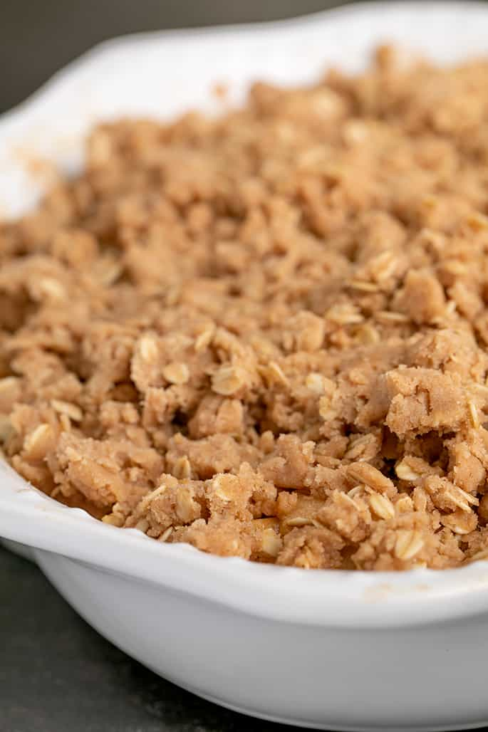 White oval baking dish with raw brown crisp topping