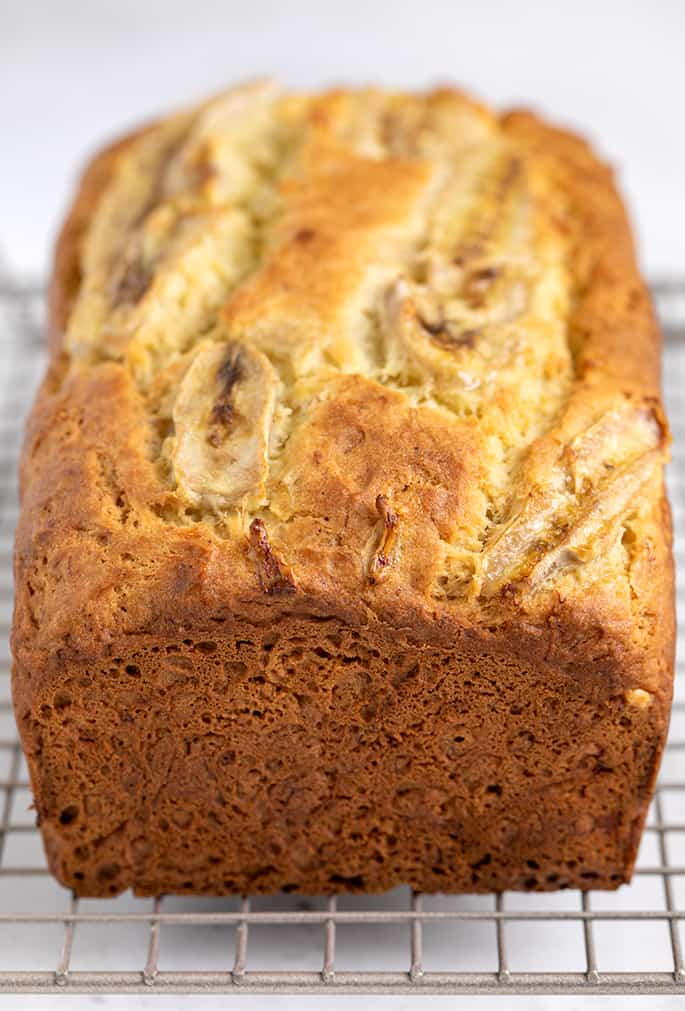 Whole baked banana bread with baked banana slices on top on wire rack on white surface