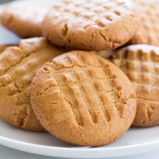 closeup image of crosshatch peanut butter cookies in a pile on a white round serving dish