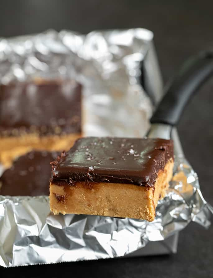 Chocolate topped peanut butter bar on metal spatula on side of foil wrapping on square metal pan