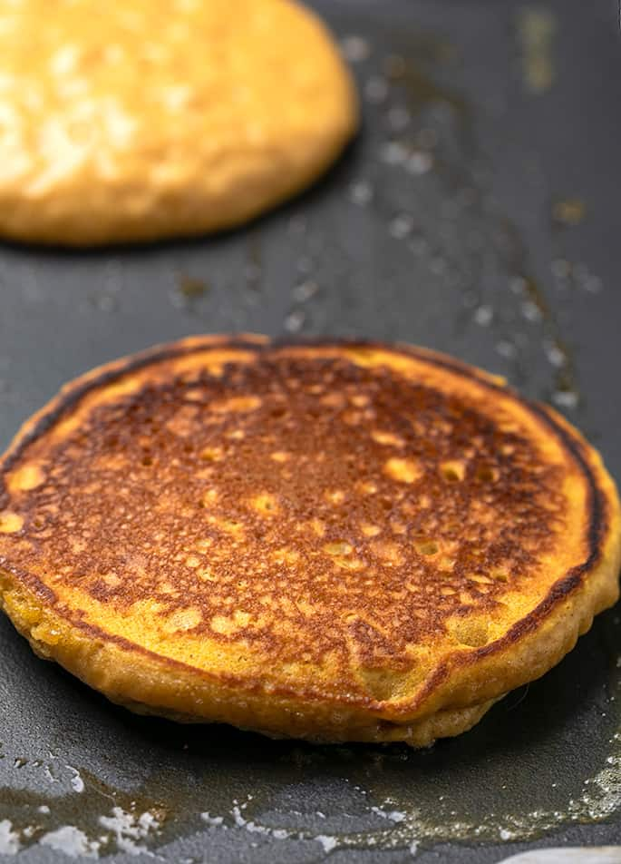 Cooked and browned pumpkin pancake on buttered griddle with one raw on top pancake in background