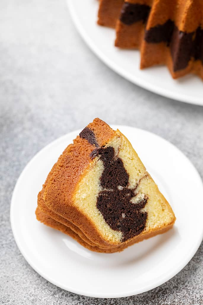 One slice of marble bundt cake on small white plate with rest of bundt cake in background on white surface