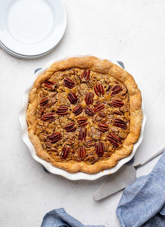 Overhead image of baked gluten free pecan pie with metal pie server, stack of small white round plates and blue cloth on white surface